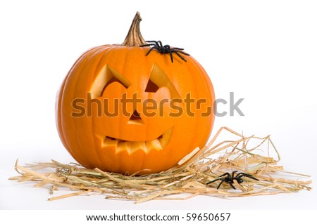 Carved Jack O Lantern on straw with spiders