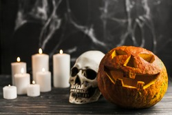 Carved pumpkin and human skull with candles