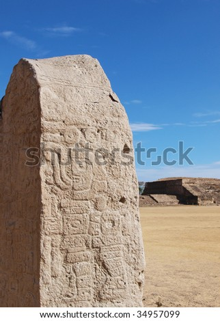 Carved stelae with pyramid in background at the ruins of the ancient Zapotec city of Monte Alban, Oaxaca, Mexico.