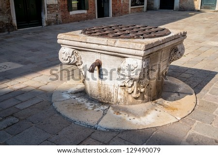 Carved well head in Venice with a fountain.