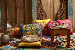carved wood design pillows embroidered with fluorescent colors in front of the wall oriental corner turkish coffee presentation