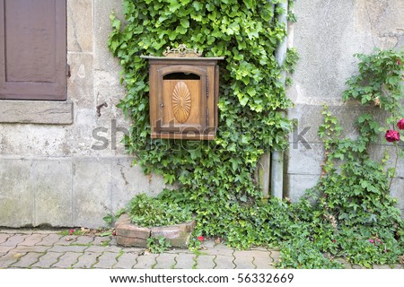 Carved wooden mailbox with Ivy growing on a stone wall. Dun-le-Palestel, La Creuse, Limousin, France.