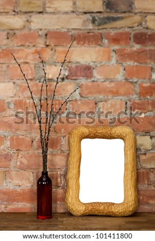 Carved wooden photo frame and brown clay bottle with willow catkins against red brick wall
