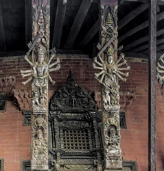 Carved wooden pillars with sculptures of the ancient temple at the 9 th century building - Bhaktapur, Nepal
