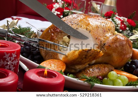 Carving roasted herb rubbed turkey garnished with fresh grapes, oranges, and cranberry is ready for Christmas dinner. Ornaments, Champagne, candles, and other Christmas decorations on feast table.