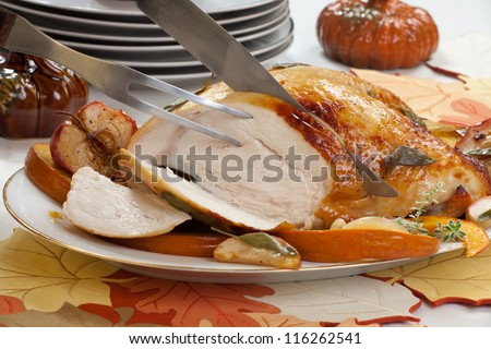 Carving sage - honey butter rub turkey breast garnished with roasted pumpkin and apples in fall themed surrounding.