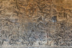 Carvings on a wall. Battle with carriages, warriors, military soldiers, inside a gallery at Angkor Wat, Siem Reap, Cambodia, South east Asia