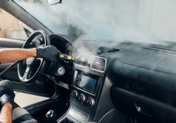 Carwash, worker cleans salon with steam cleaner