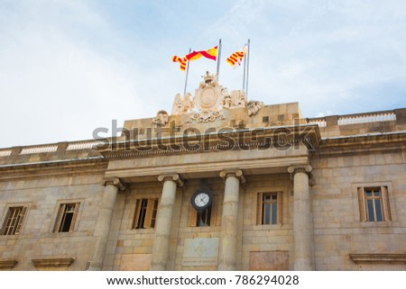 Casa de la Ciudad with Flags of Spain, Catalonia Barcelona and emblem of the city of Barcelona on the building top. Neoclassical facade City hall was built in 1847 and Located on Plaza de Sant Jaume