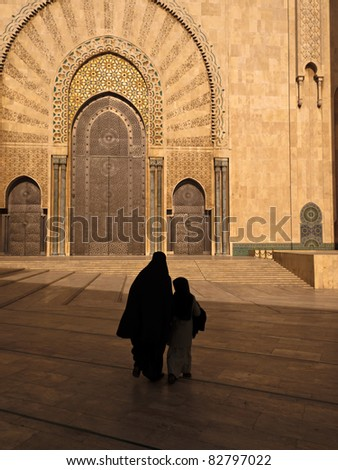 Casablanca, Morocco:  Silhouette of woman in burka and child walking toward Hassan II Mosque in Casablanca, Morocco.