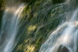 """Cascade in Bad Urach southern Germany is a popular natural attraction and waterfall sight """"Uracher Wasserfall"""". Waterfall with splashes and spattering drops in bright morning sunlight after heavy rain"""
