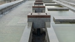 Cascade system of urban fountains in the main square of the city. A modern fountain in the city. Citylife concept.