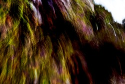 Cascading, warm multicolored, mountainside vegetation light-streak pattern with heavy shadows - abstract, motion-blurred background texture