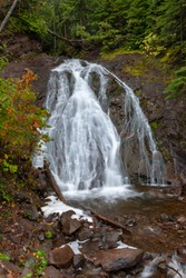 Cascading water flows rapidly over Jacobs Falls near Eagle River Michigan. Autumn colors and rock walls in the background. Near the popular Jam Pot