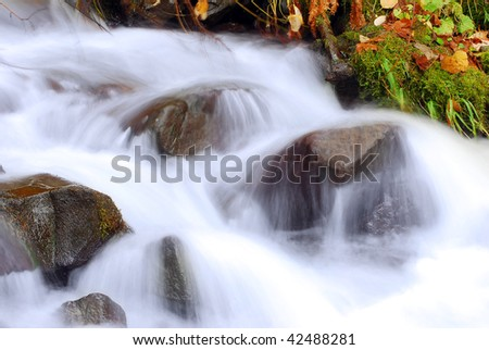 stock-photo-cascading-waterfall-and-autumn-leaves-closeup-very-smooth-water-with-wet-rocks-fall-river-42488281.jpg