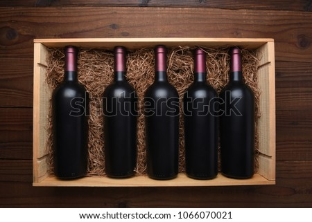Case of Red Wine: Top view of a wood case of red wine bottles on a dark wood table, the case is filled with packing straw.