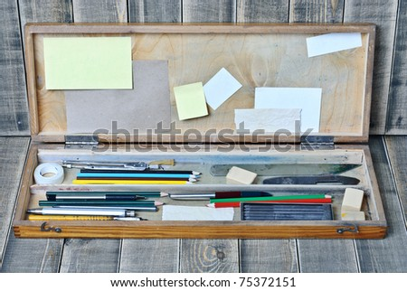 Case with a range of accessories for the artist on a wooden background - stock photo