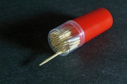 Case with wooden toothpicks on a dark gray background close-up. Wooden toothpicks in plastic case.