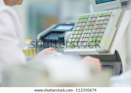 Cash-desk with cashier and terminal in supermarket - stock photo
