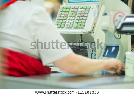 Cash-desk with cashier and terminal in supermarket. Serve customer