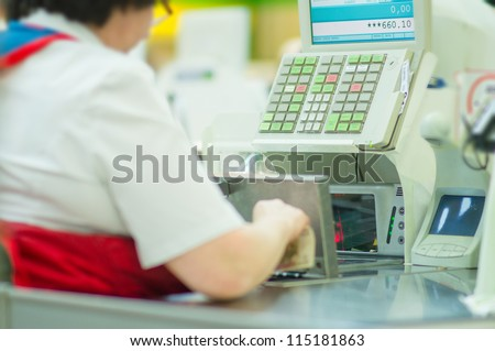 Cash-desk with cashier and terminal in supermarket. Serve customer, holding money in hand