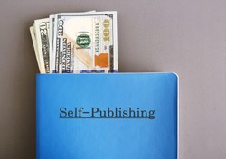 Cash dollars money in blue notebook with text typed SELF - PUBLISHING, on grey background, concept of make more income from writing book or ebook and self-publish online or traditional way