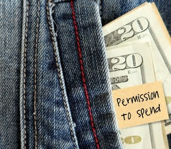 cash dollars money in jean pocket with stick note PERMISSION TO SPEND, means a little fun money to give yourself to spend , to shop guilt-free, for money saver
