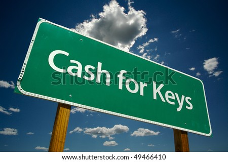 Cash for Keys Green Road Sign on Dramatic Blue Sky with Clouds.