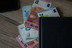 Cash in the book, used as bookmark, financial growth through the education and hard work