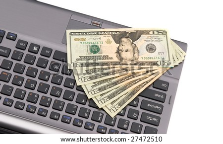 Cash lying on a keyboard during an online Internet shopping spree.