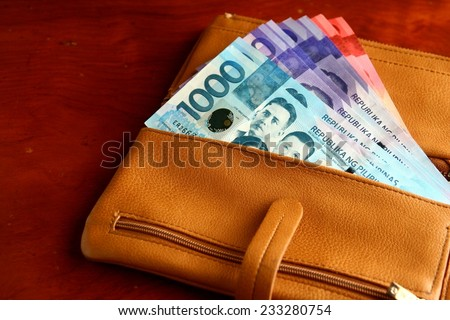 Cash money in a leather wallet Photo of a bunch of cash money in a leather wallet