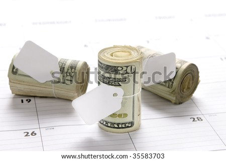 Cash money rolls on a desk calendar with blank tags for copy