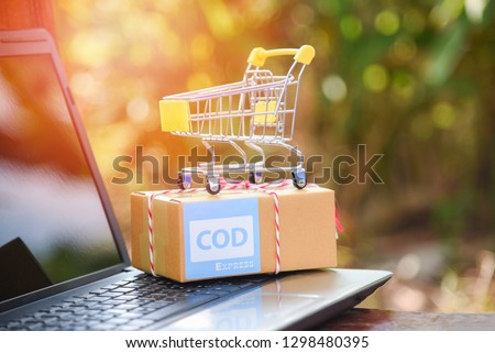 Cash on delivery express shipping laptop ecommerce shopping online and order concept / selling online with shopping cart packing cardboard box prepare parcel to delivery service customer