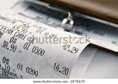 Cash receipt illustrating the spent money on background of a purse