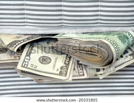 Cash stashed for safe keeping in between mattresses. - stock photo