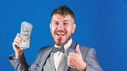Cash transaction business. Man happy winner rich hold pile of dollar banknotes blue background. Easy cash loans. Win lottery concept. Businessman got cash money. Get cash easy and quickly.