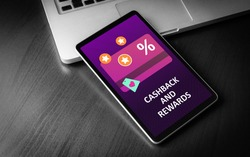 Cashback and Rewards - loyalty program and retail customer money refund service concept. Tablet PC lying on a wooden table with cashback discount card and rewarding marketing points on the screen