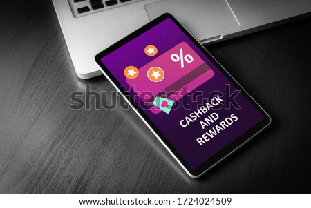 Cashback and Rewards - loyalty program and retail customer money refund service concept. Tablet PC lying on a wooden table with discount card with rewarding marketing points on the screen