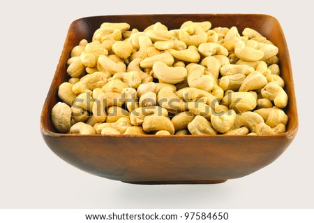 Cashew in a wooden bowl, which stands on a table against a white background