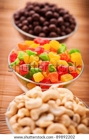 "cashew nuts, candied sweet and colorful candy ""chocolate peanut"" in three different transparent glass tub on bamboo table cloth"