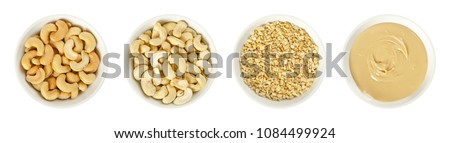Cashew nuts in white porcelain bowls. Raw and processed nuts. Whole, roughly chopped, roasted, salted and as butter. Anacardium occidentale. Seeds. Isolated food photo, close up from above over white.