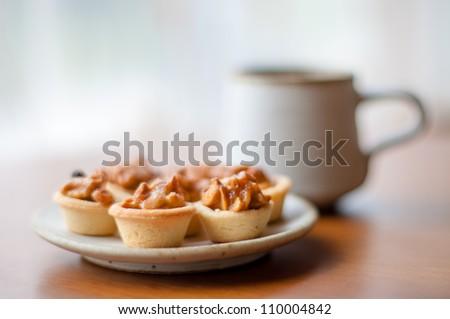 Cashew tart on serving plate. [Focus with a cashew tart]