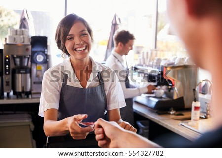 Cashier Accepts Card Payment From Customer In Delicatessen