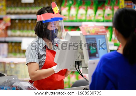 Cashier or supermarket staff in medical protective mask and face shield working at supermarket. covid-19 spreading outbreak