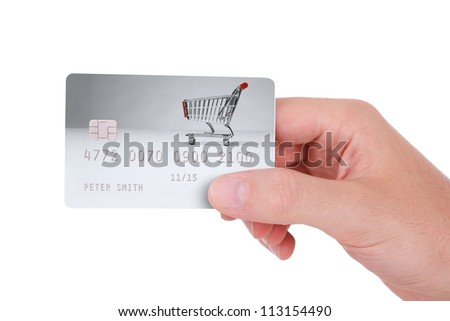 Cashless payment - credit card hold in right hand. I am author of photo with shopping cart used on credit card and used data are fictitious. - stock photo