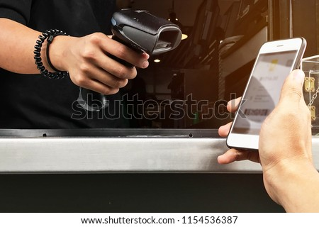 Cashless society concept. Man hand holding a smartphone, using mobile application to pay for his drink at the cashier.