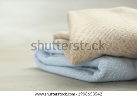 Cashmere clothes on wooden table, closeup view ストックフォト ©