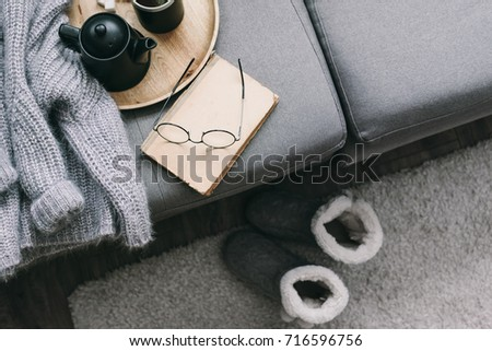 Cashmere sweater, reading and serving tray on gray sofa. Warm weekend at home. Detail of cozy winter interior.
