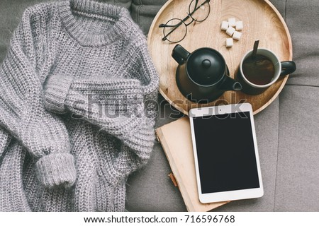 Cashmere sweater, reading and serving tray on gray sofa. Warm weekend at home. Detail of cozy winter interior. Watching movies on tablet pc. #716596768