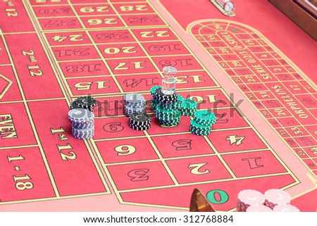 Casino American Roulette gambling table with a playing chips on the layout.